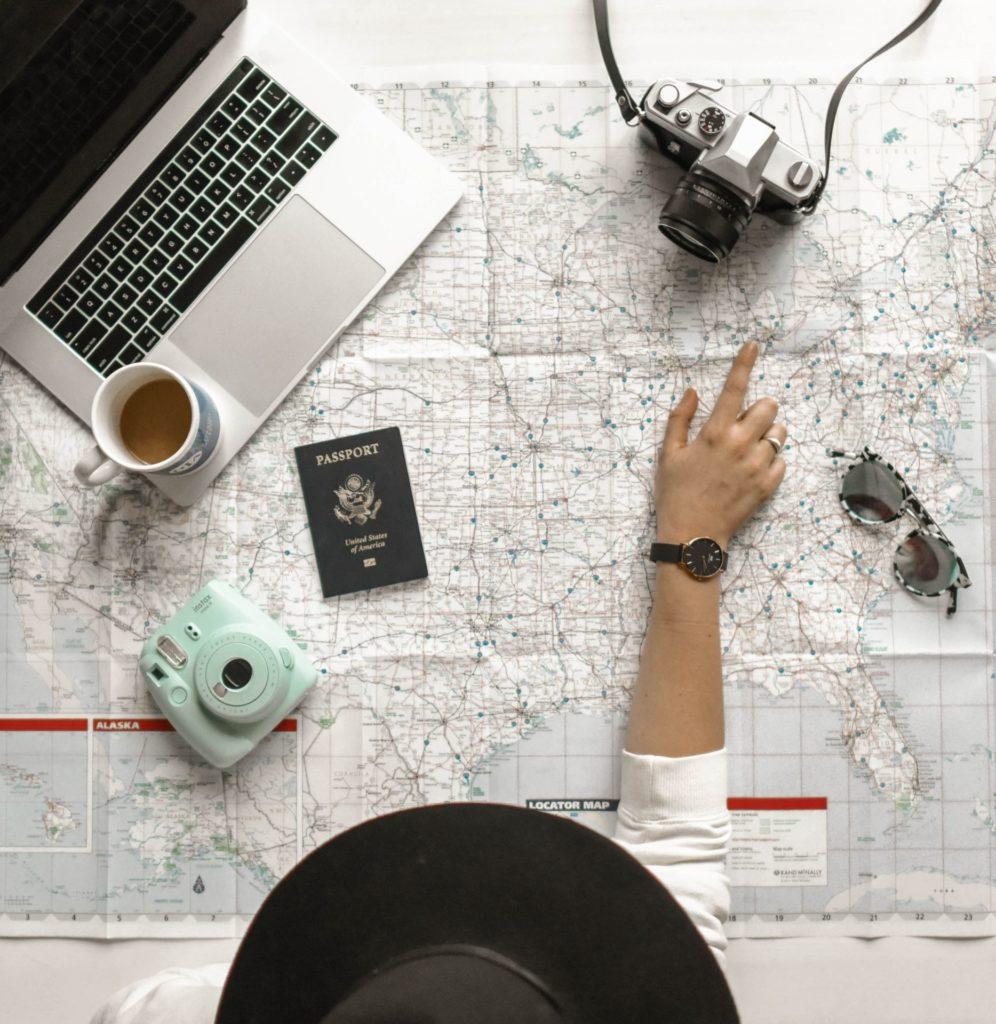 Fille qui prépare son séjour à l'étranger avec appareil photo, passeport, carte et ordinateur